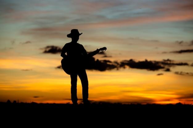 Silhouet meisje gitarist op een zonsondergang Gratis Foto