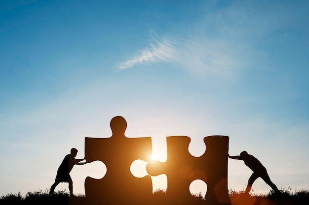 Silhouet twee mannen duwen om puzzel te verbinden met zonlicht en blauwe lucht. Premium Foto