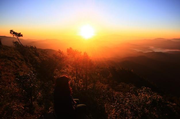 Silhouet van aziatische vrouwenzitting alleen in natuurlijke gouden zonsopgang Premium Foto