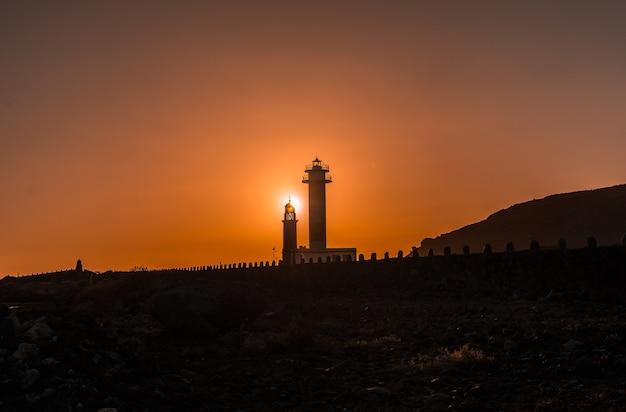 Silhouet van de fuencaliente-vuurtoren bij zonsondergang, op de route van de vulkanen ten zuiden van het eiland la palma, canarische eilanden, spanje Premium Foto