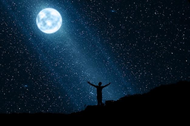 Silhouet van de gelukkige mens die van de nacht met maan en sterren geniet Premium Foto