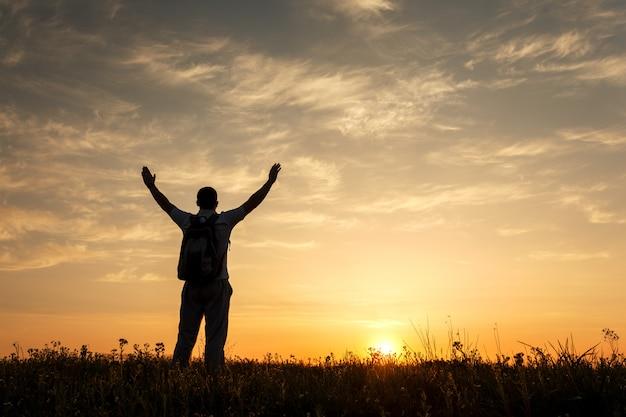 Silhouet van de mens met opgeheven armen en mooie hemel Premium Foto
