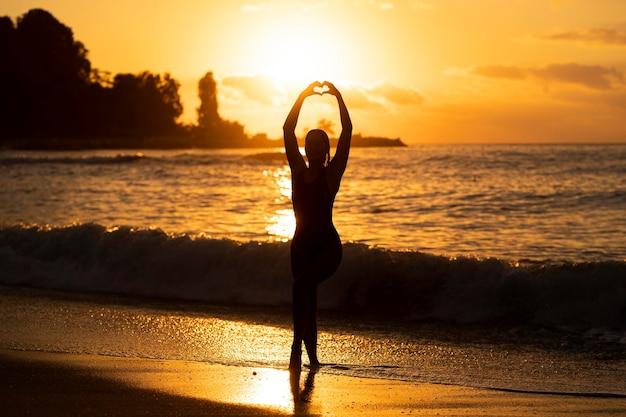 Silhouet van de vrouw die zich voordeed aan het strand Premium Foto