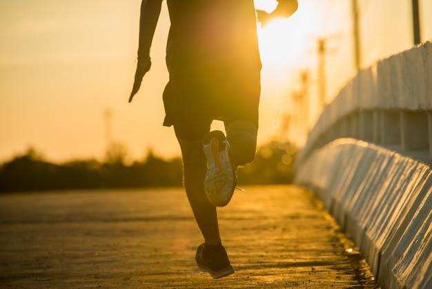 Silhouet van een jonge fitness man loopt op zonsopgang Gratis Foto