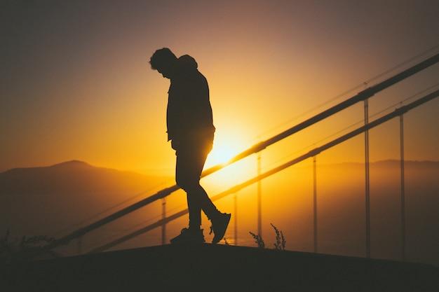 Silhouet van een jonge man lopen op de trap achter trapleuningen met prachtig uitzicht op de zonsondergang Gratis Foto