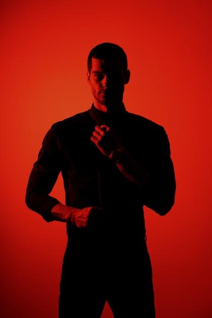 Silhouet van een jonge zelfverzekerde knappe zakenman die zwart overhemd in rood licht draagt Gratis Foto