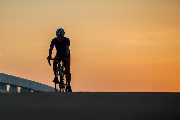 Silhouet van een man rijdt op een fiets bij zonsondergang. oranje-blauwe hemelachtergrond. Gratis Foto