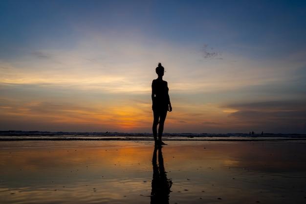 Silhouet van een meisje dat zich in het water op een strand bevindt aangezien de zon ondergaat Gratis Foto