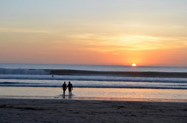 Silhouet van een paar wandelen in het water in de buurt van de kust met een mooie hemel Gratis Foto