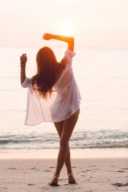 Silhouet van een slank meisje dat zich op een strand met ondergaande zon bevindt. ze draagt een wit overhemd. ze heeft lang haar dat in de lucht vliegt. haar armen strekten zich in de lucht Gratis Foto