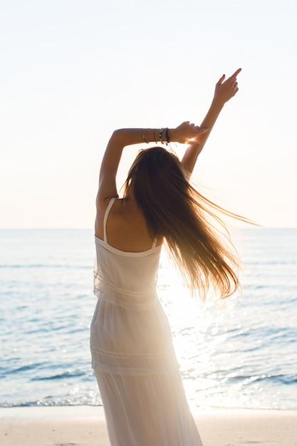 Silhouet van een slank meisje dat zich op een strand met ondergaande zon bevindt. ze draagt een witte jurk. ze heeft lang haar dat in de lucht vliegt. haar armen strekten zich in de lucht Gratis Foto