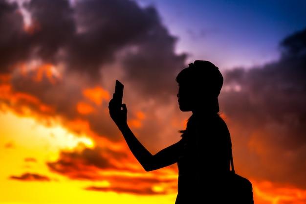 Silhouet van een telefoon van de de vrouwenholding van de toerist die beelden met de dramatische achtergrond van de zonsonderganghemel neemt Premium Foto