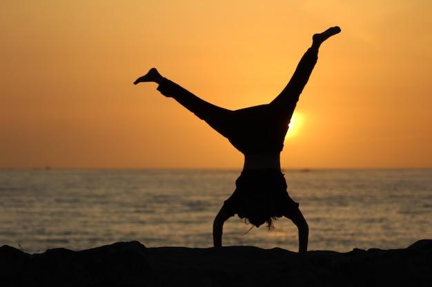 Silhouet van een vrouw doet een radslag met een wazige zee en een heldere hemel Gratis Foto
