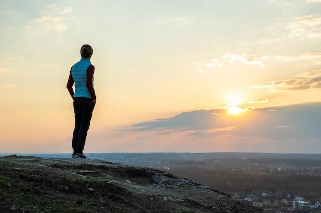 Silhouet van een vrouw wandelaar staan genieten van zonsondergang buiten. vrouwelijke toerist op landelijk gebied in de avondaard. toerisme, reizen en een gezonde levensstijl. Premium Foto