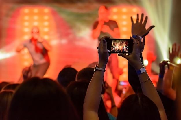 Silhouet van handen met een smartphone tijdens een concert Premium Foto