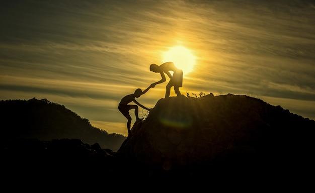 Silhouet van helpende hand tussen twee jongensklimmer Premium Foto