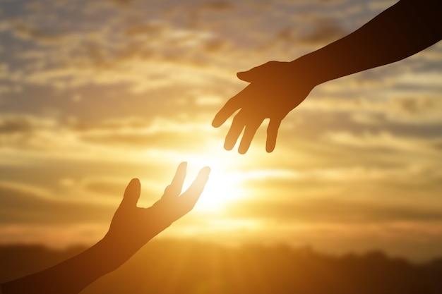 Silhouet van het geven van een helpende hand, hoop en steun elkaar op zonsondergang achtergrond Premium Foto