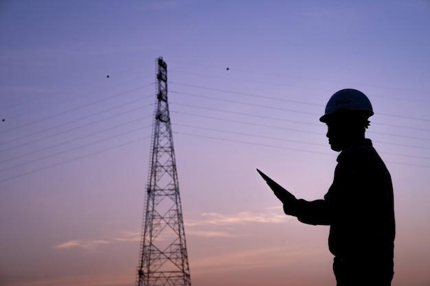 Silhouet van ingenieurs die orden door radio voor bouwbemanningen veilig werken op hallo-voltagepost. industrie en veiligheid op het werk concept. Premium Foto
