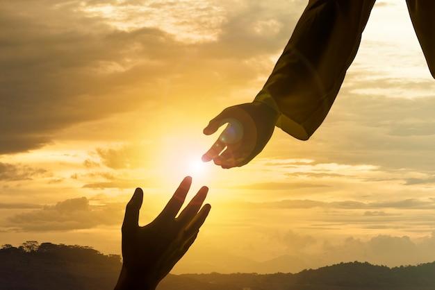 Silhouet van jezus die helpende hand geeft Premium Foto