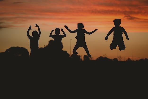 Silhouet van kinderen die zich voordeed op de heuvel omringd door groen tijdens een gouden zonsondergang Gratis Foto