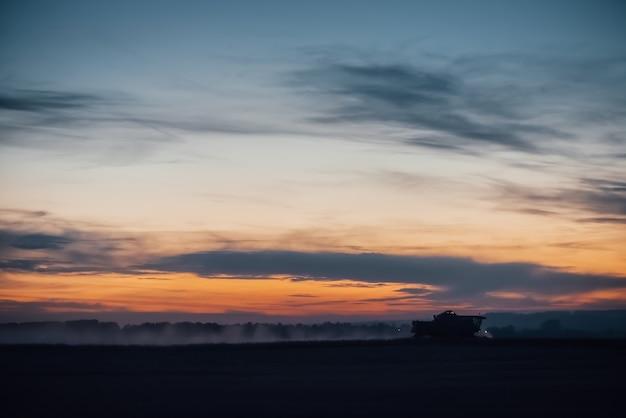 Silhouet van maaimachinemachine om tarwe op zonsondergang te oogsten. Premium Foto