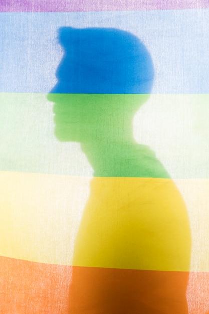 Silhouet van man achter regenboogvlag Gratis Foto