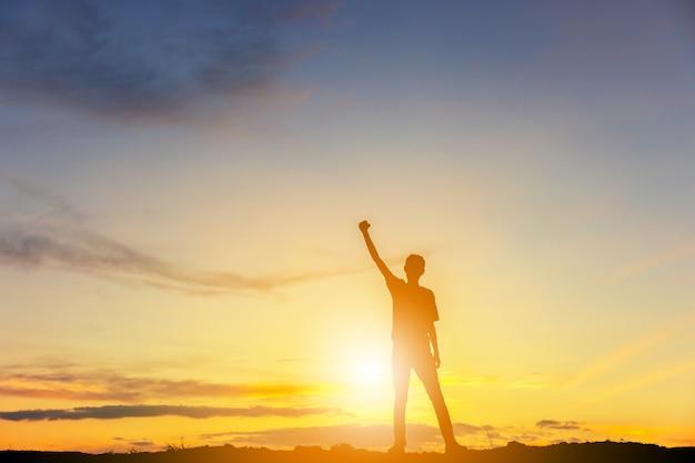 Silhouet van man viering succes geluk op een bergtop avondhemel zonsondergang achtergrond. Premium Foto