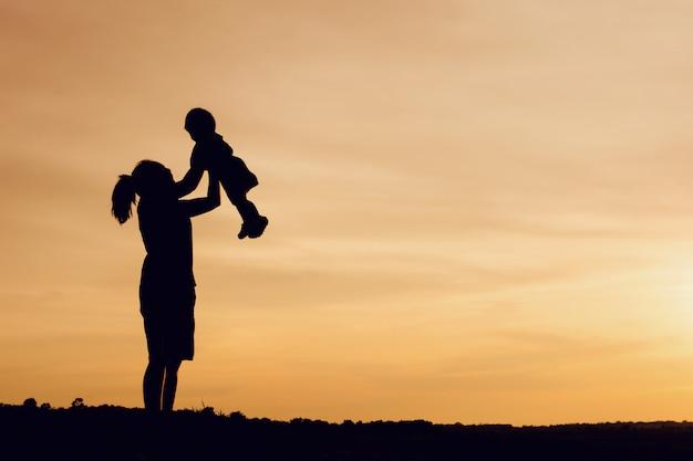 Silhouet van moeder en dochter opheffend kind in lucht over toneelzonsonderganghemel bij rivieroever. Premium Foto