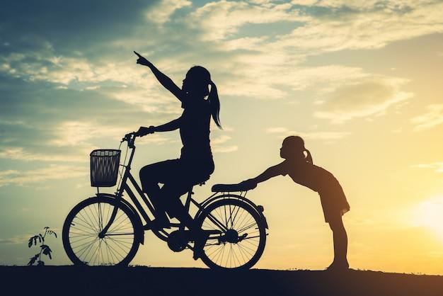 Silhouet van moeder met haar dochter en fiets Gratis Foto