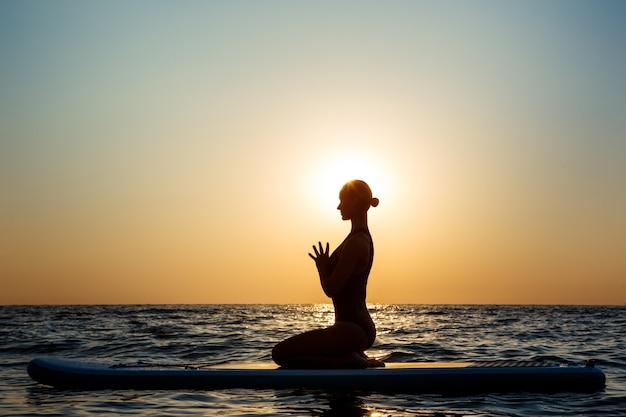 Silhouet van mooie vrouw het beoefenen van yoga op surfplank bij zonsopgang. Gratis Foto
