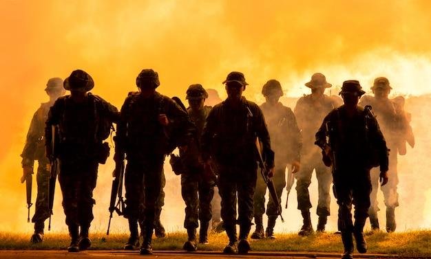 Silhouet van niet-herkende soldaten met geweer lopen door rook Premium Foto
