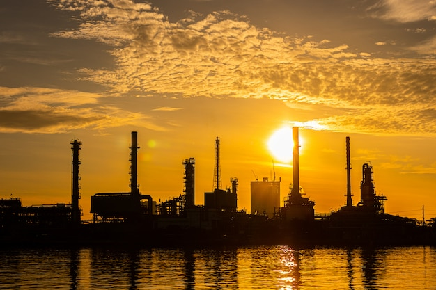 Silhouet van olie- en gasindustrie raffinaderij-industrie plant met glitter verlichting en zonsopgang in de ochtend Premium Foto