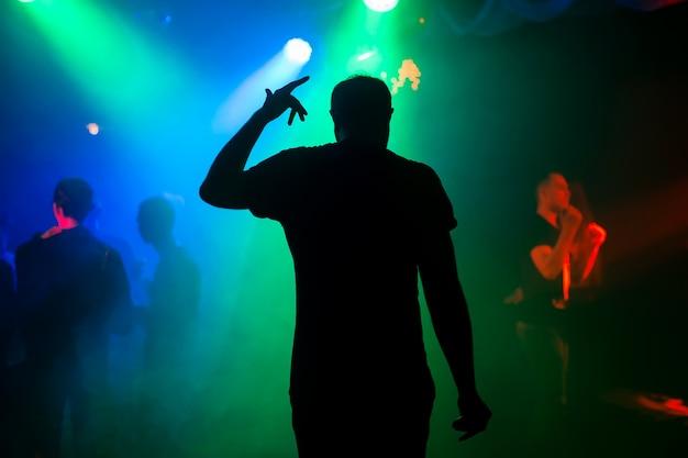 Silhouet van presentator op het stadium van de nachtclub bij overleg terug bij het evenement Premium Foto