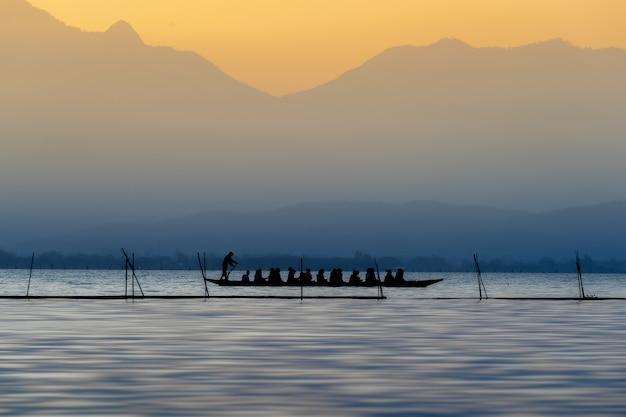 Silhouet van toeristen op de houten boot bij phayao-meer, thailand. Premium Foto