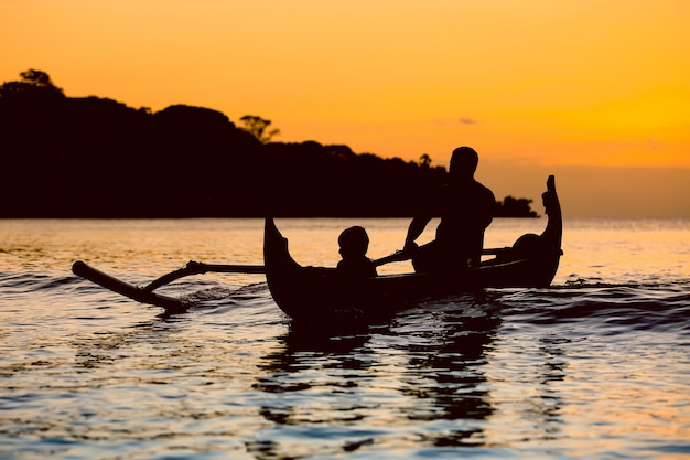 Silhouet van traditionele vissersboot bij zonsondergang in bali, jimbaran strand Premium Foto