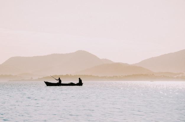 Silhouet van vissers in een kleine boot Gratis Foto