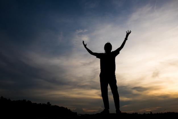 Silhouet van vrouw die met god bidt Gratis Foto