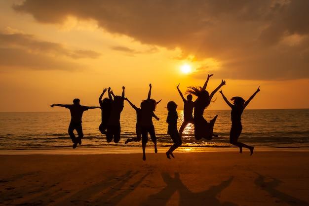 Silhouetfoto van de teamviering op het strand bij zonsondergang Premium Foto