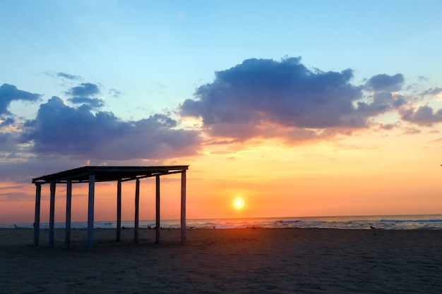 Silhouetgazebo op een leeg zandig strand op een zonsondergangachtergrond. Premium Foto
