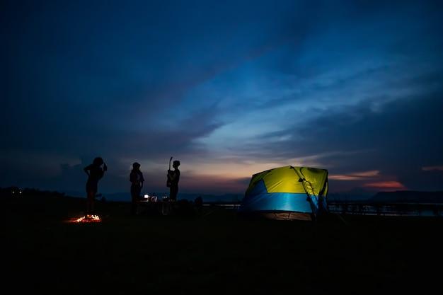 Silhouetgroep aziatische vriendentoerist die en gitaar samen met geluk in de zomer drinken spelen terwijl het hebben van het kamperen dichtbij meer Premium Foto