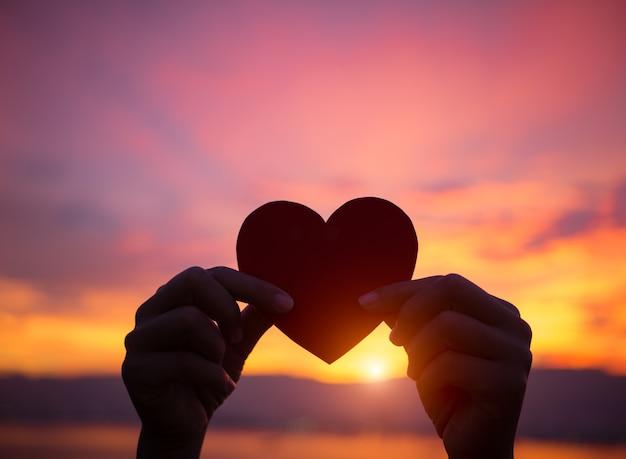 Zeer Silhouethand die mooi hart houden tijdens zonsondergangachtergrond #BX47