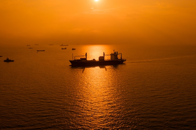 Silhouetlogistiek die ladings open zee en over de zonsondergangachtergrond verschepen Premium Foto