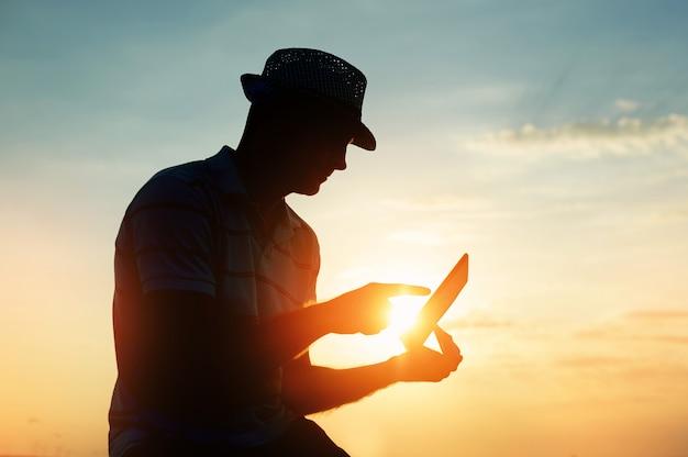Silhouetmens die aan zijn laptop op het strand tijdens zonsondergang werken Premium Foto