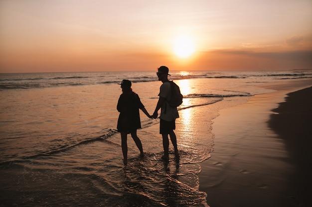 Silhouetportret van jong romantisch paar dat op het strand loopt. meisje en haar vriend poseren bij gouden kleurrijke zonsondergang Gratis Foto