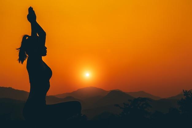 Silhouette - yogameisje oefent op het dak terwijl zonsondergang. Gratis Foto