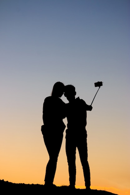 Silhouetteert man en vrouw die selfie met smartphone op zonsonderganghemel nemen Premium Foto