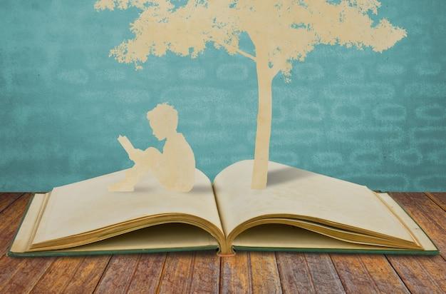 Silhouetten van een boom en een man op een boek Gratis Foto