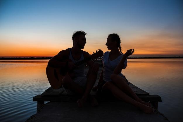 Silhouetten van het jonge mooie paar rusten die zich verheugen bij zonsopgang dichtbij meer Gratis Foto