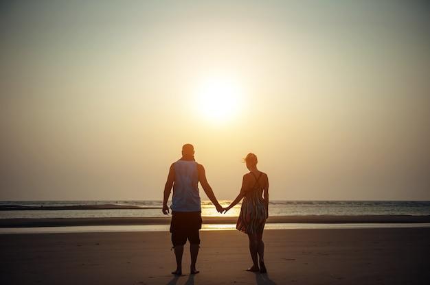 Silhouetten van man en vrouw op het strand. jong koppel in liefde hand in hand bij zonsondergang. concept van liefde, familie, relaties. romantiek, huwelijksreis Premium Foto