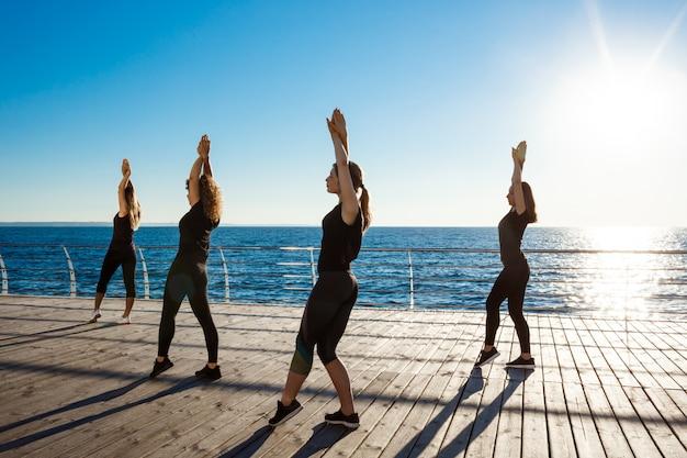 Silhouetten van sportieve vrouwen die zumba dichtbij overzees dansen bij zonsopgang Gratis Foto